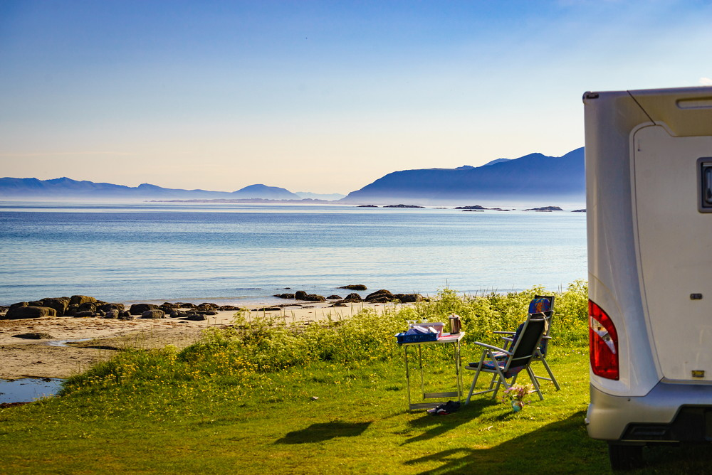 Camping on sea shore. Camper car with tourist chairs and table on norwegian fjord. Holidays relaxation on trip. Lofoten Norway